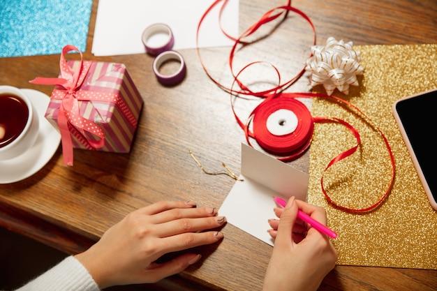 Donna che fa biglietto di auguri per capodanno e natale 2021 per amici o familiari, prenotazione rottami, fai da te. scrivere una lettera con i migliori auguri, utilizzando gli strumenti per progettare la sua carta fatta in casa. vacanze, celebrazione