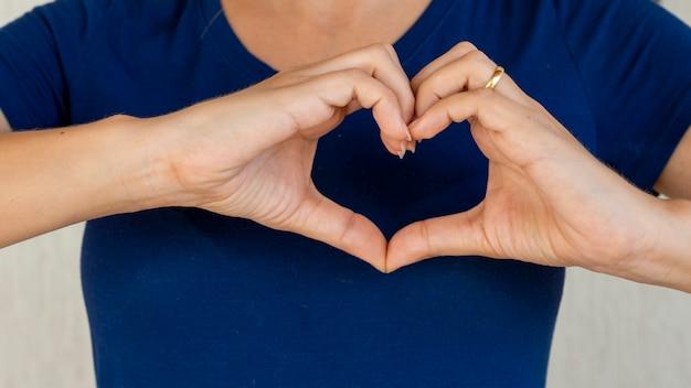 Donna che fa le mani a forma di cuore, assicurazione sanitaria del cuore, responsabilità sociale, donazione, volontario di beneficenza felice, giornata mondiale del cuore, donatore di organi, apprezzamento, salute mentale mondiale, giornata del cancro