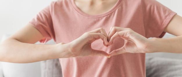 Donna che fa le mani a forma di cuore amore cuore assicurazione sanitaria donazione di responsabilità sociale
