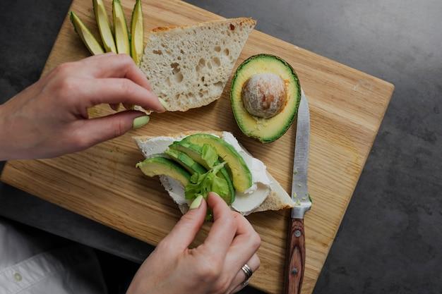 Donna che prepara un sano toast con avocado