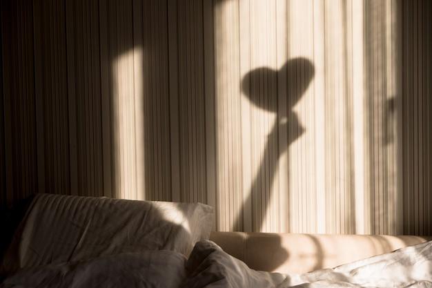 Donna che fa l'ombra del cuore sul muro. giornata mondiale della salute mentale, speranza e amore.