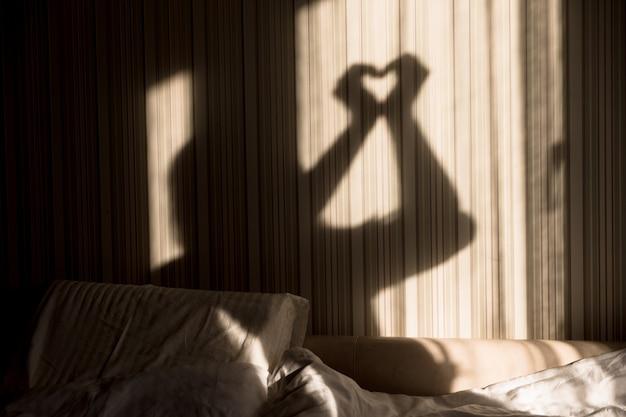 Donna che fa ombra di cuore con le sue mani sul muro. giornata mondiale della salute mentale, speranza e amore