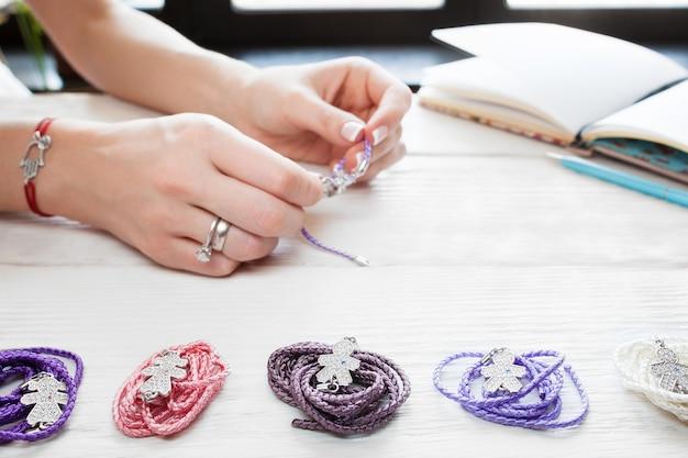 Donna che fa il braccialetto fatto in casa. varietà di accessori sul tavolo in legno bianco, posto di lavoro artigianale. creazione di gioielli fatti a mano. lavoro domestico femminile per il tempo libero