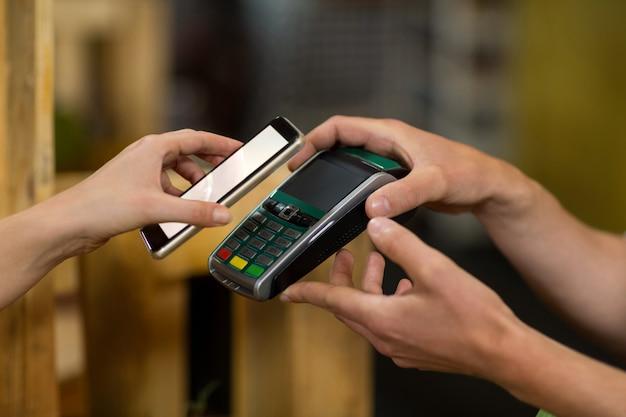 Donna che effettua un pagamento utilizzando la tecnologia nfc nel negozio di alimentari