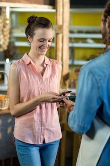 Donna che effettua un pagamento utilizzando la tecnologia nfc