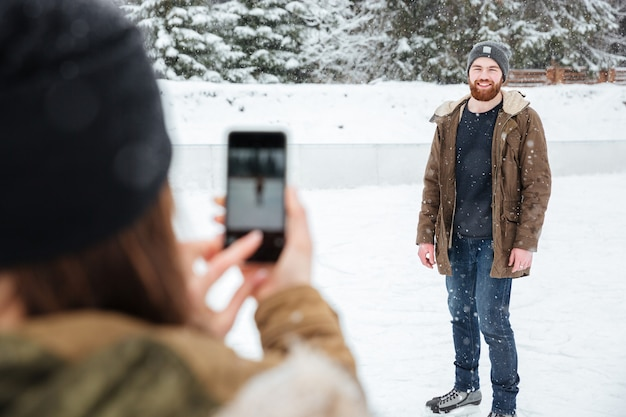 Donna che fa foto sullo smartphone di un uomo all'aperto