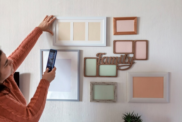 Donna che fa foto del muro bianco con set di diverse cornici vuote verticali e orizzontali, progetto di galleria fotografica di famiglia per catturare il momento, modello di mockup sul muro bianco, stile di vita