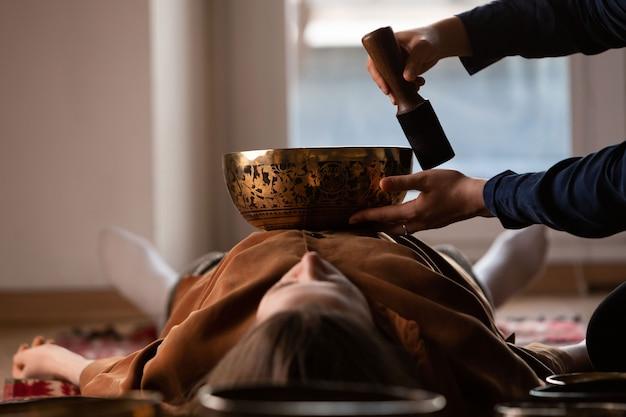 Donna che fa massaggio rilassante, meditazione, terapia del suono con campane tibetane
