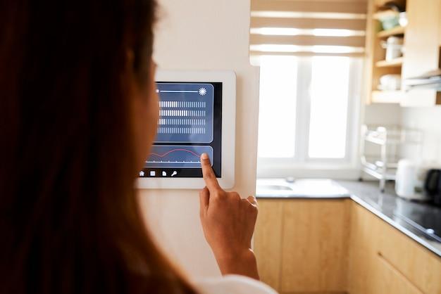 Donna che fa impostazione della sua casa con l'applicazione online