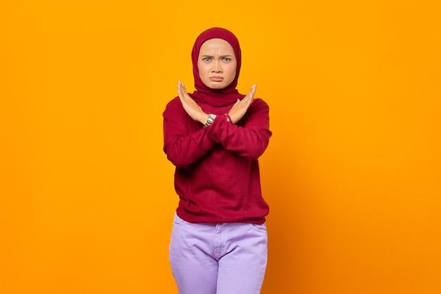 Donna che fa il segnale di stop con le mani incrociate ragazza seria che nega di rifiutare qualsiasi azione guardando la telecamera