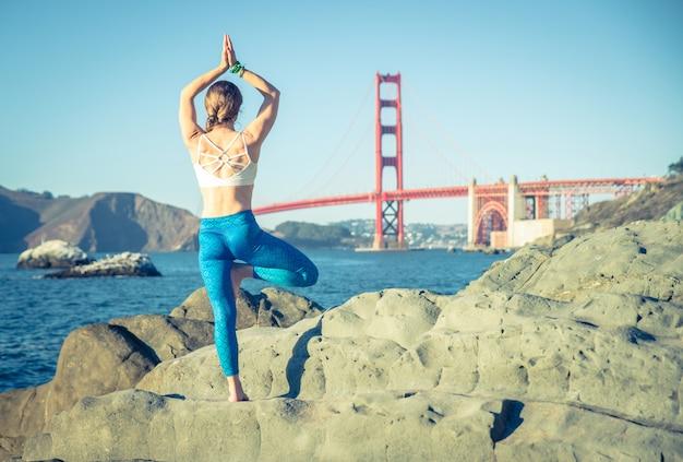 La donna che fa l'yoga posa in baker beach, san francisco