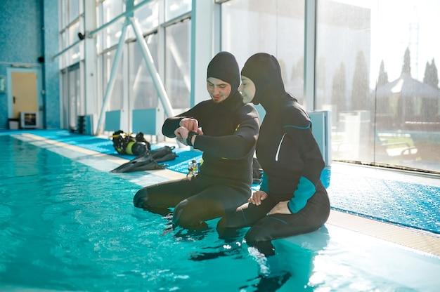 Donna e divemaster maschio in attrezzatura subacquea che si preparano per l'immersione, scuola di immersioni. insegnare alle persone a nuotare sott'acqua, interno della piscina coperta sullo sfondo