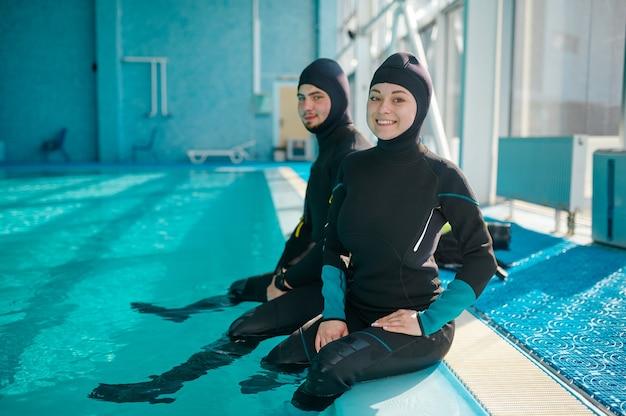 Donna e divemaster maschio in attrezzatura subacquea che si preparano per l'immersione, scuola di immersioni. insegnare alle persone a nuotare sott'acqua, interno della piscina coperta