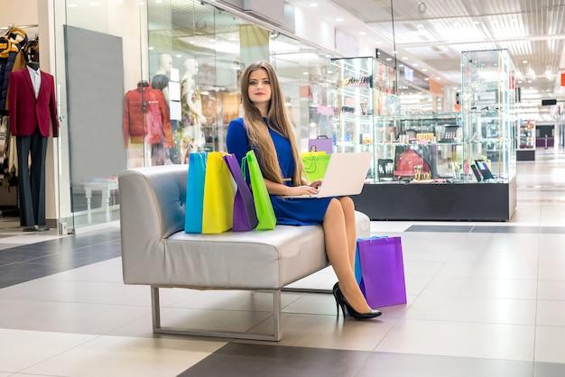 Donna in un centro commerciale che fa shopping online con il laptop