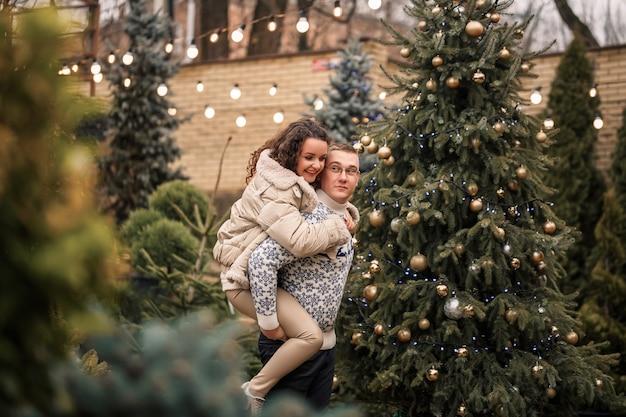 Una donna e un uomo sono in piedi vicino all'albero di natale, sono felici, l'umore del nuovo anno