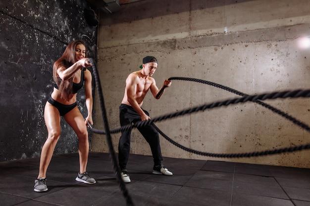 Le coppie dell'uomo e della donna si preparano insieme facendo l'allenamento della corda di combattimento