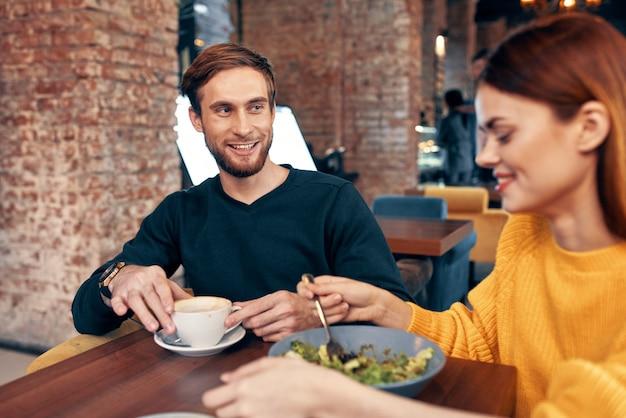 Donna e uomo che cenano nel ristorante insalata pasto cibo tazza di caffè