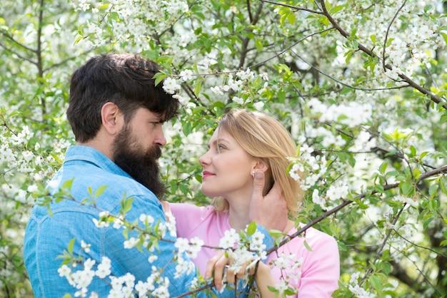 Donna e uomo che godono di relazioni perfette e trascorrono vacanze primaverili. giovani coppie felici vicino all'albero del fiore.