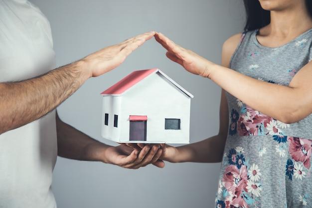 Modello di casa mano uomo e donna su grigio