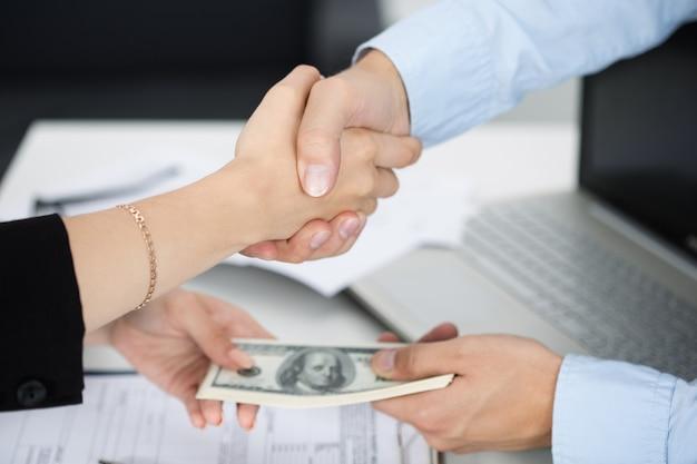 Stretta di mano dell'uomo e della donna si chiuda con i soldi nelle altre mani. affare, venalità, tangente, concetto di corruzione