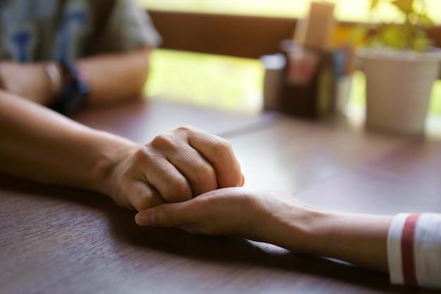 La donna e l'uomo che si tengono per mano si prendono cura insieme