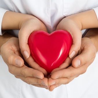 Donna e uomo che tengono cuore rosso insieme nelle loro mani. amore, assistenza e concetto di assistenza sanitaria