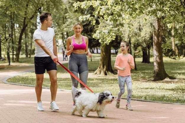 Donna, uomo e bambina che fanno jogging con il loro cane nel parco