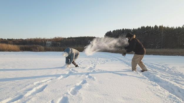 Una donna e un uomo con maschere mediche giocano a palle di neve in un parco invernale, indossare una maschera medica nei luoghi pubblici aiuta a prevenire lo sviluppo dell'epidemia di coronavirus