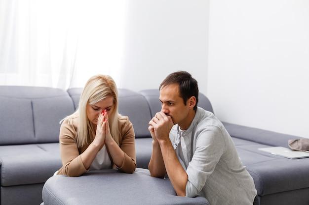 Donna e uomo pregano a casa