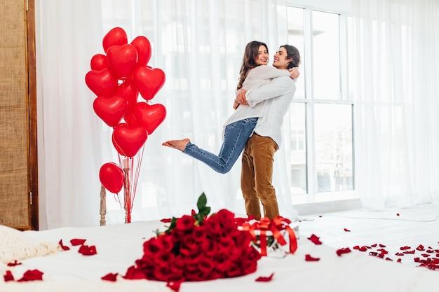 Donna e uomo in piedi nella stanza con bouquet di rose rosse, confezione regalo e palloncini a forma di cuore
