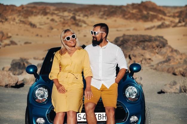 Una donna e un uomo con gli occhiali in un'auto decappottabile durante un viaggio nell'isola di tenerife. il cratere del vulcano teide, isole canarie, spagna.
