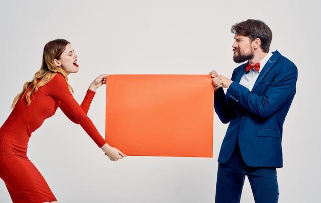 Donna e uomo con un foglio di carta rosso e pubblicità mockup su uno spazio grigio