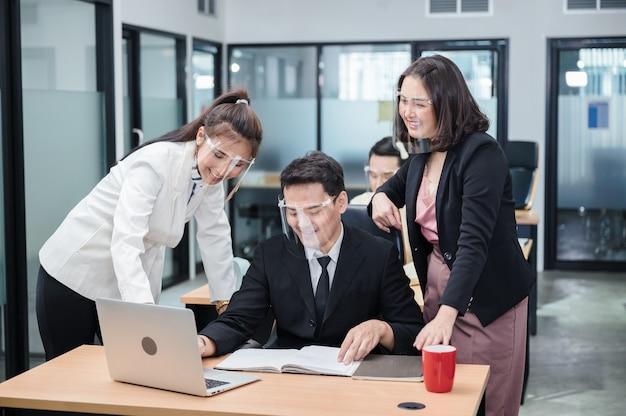 Donna manager e dipendenti che indossano visiera medica stanno discutendo sulla scrivania in ufficio