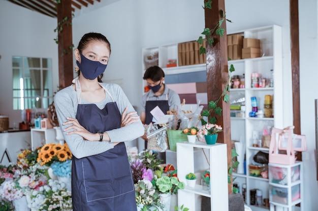 Donna manager che indossa la maschera per il viso fiorista in piedi braccio incrociato con il suo personale
