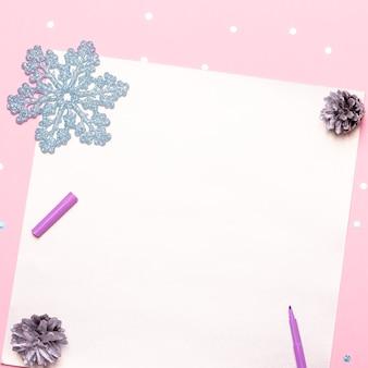Mani curate della donna che tengono la penna e scrivono obiettivi e piani per il nuovo anno. piatto disteso su scrivania rosa pastello con coriandoli e decorazioni natalizie, vista dall'alto, spazio copia