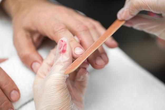 Manicure donna facendo manicure per uomo nel salone di bellezza
