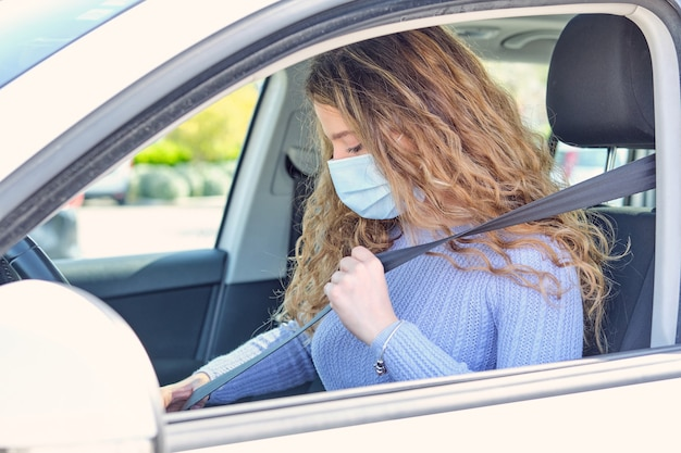 Donna in cintura di fissaggio della maschera nel sedile del conducente dell'auto