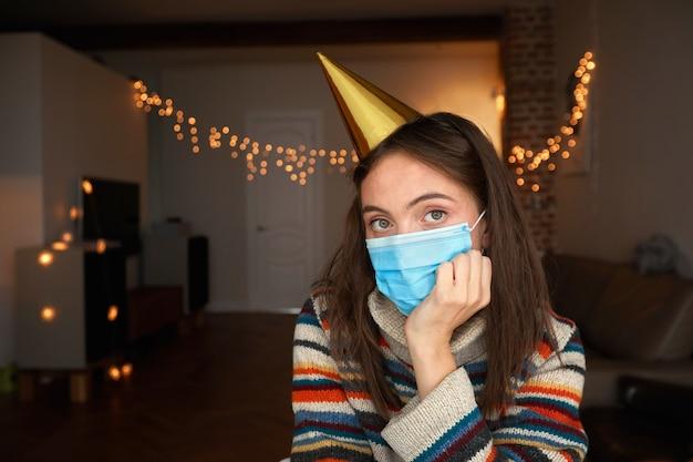 Donna in maschera e cappello da festa si siede in una stanza buia con luci e tiene la testa in mano a casa