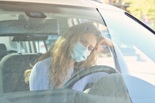 Donna in maschera seduta sul sedile del conducente dell'auto