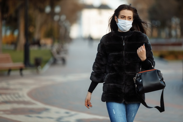 Donna in una maschera che cammina nella città di te