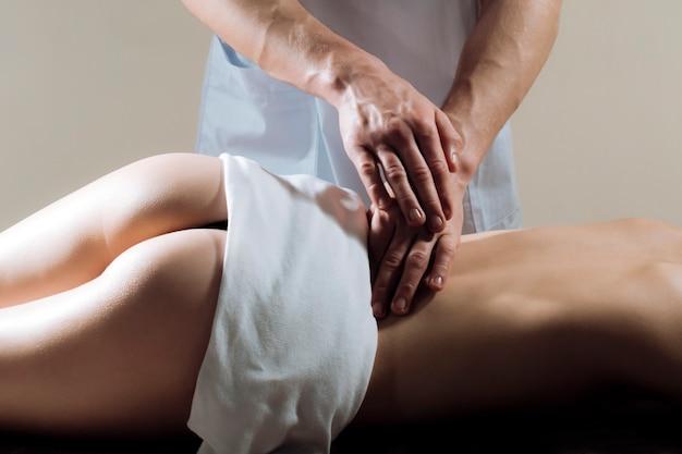 Massaggio donna, massaggio ragazza. corpo termale, concetto di salute e relax, centro termale. massaggiatore che fa massaggi sul corpo di una donna, culo sexy. massaggi ravvicinati.