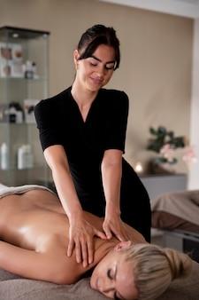 Donna che massaggia il suo cliente nel suo salone