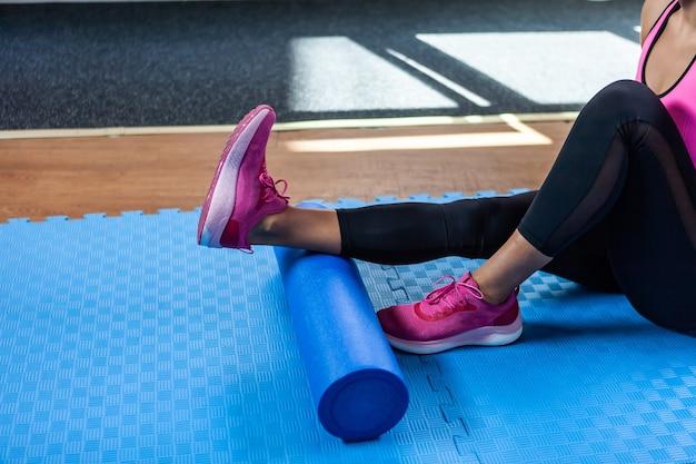 Donna che massaggia le gambe con il rullo massaggiante dopo un duro allenamento in classe di fitness