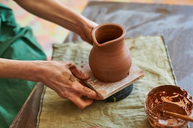Una donna maestra di ceramica in un grembiule verde mette ad asciugare una brocca di argilla rossa.