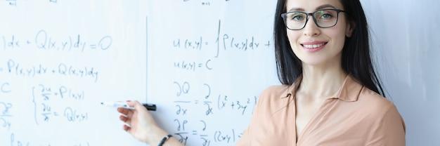 Matematico donna con gli occhiali in piedi alla lavagna con formule e tenendo libro aperto