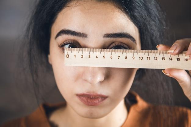 La donna misura gli occhi con un righello