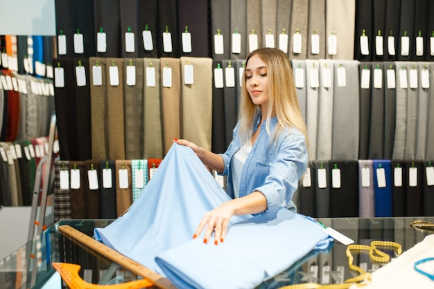 La donna misura il tessuto nel negozio di tessuti. ripiano con panno per cucire