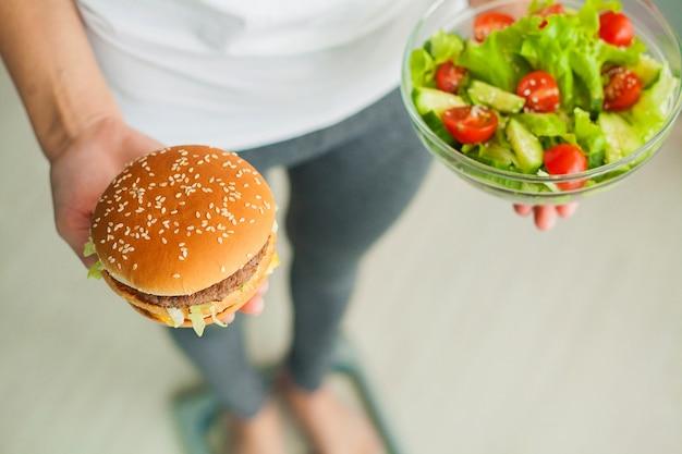 Donna che misura il peso corporeo sulla bilancia tenendo hamburger e insalata, i dolci sono cibo spazzatura malsano, dieta, alimentazione sana, stile di vita, perdita di peso, obesità, vista dall'alto