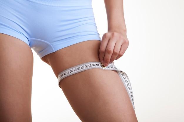 Donna che misura la sua gamba isolata su sfondo bianco