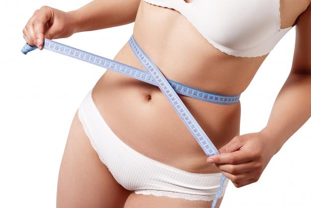 Donna che misura il suo corpo esile isolato sulla parete bianca